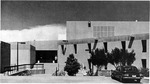 Wide-view of southern exterior main entrance (not Clinic entrance) with car and figures walking. by University of New Mexico School of Law