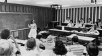 View of students and female professor from back of classroom 2405 during a lecture. by University of New Mexico School of Law