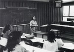 View of students and female professor in classroom 2406 during a lecture.