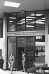 Students exiting through interior wooden doors with Zuni proverb on lintel by University of New Mexico School of Law