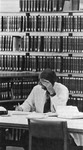 Single male law student studying with wall of books behind. by University of New Mexico School of Law