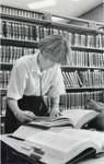 Single female law student reviewing books. by University of New Mexico School of Law