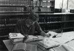 Single male law student studying at table with various levels of books behind. by University of New Mexico School of Law