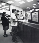 View of ciruclation desk, with a shot of staff and students conversing.