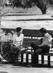 Two students sitting on an outside bench. by University of New Mexico School of Law