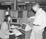 Two students talking at computer.