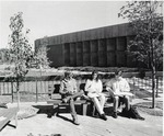 Three students sitting on an outside bench, North Patio.