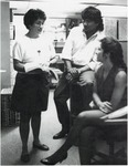 Three students chatting indoors. by University of New Mexico School of Law